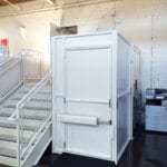 Symmetry Vertical Platform Lift in white with tall gate midmount operator installed by Arrow Lift