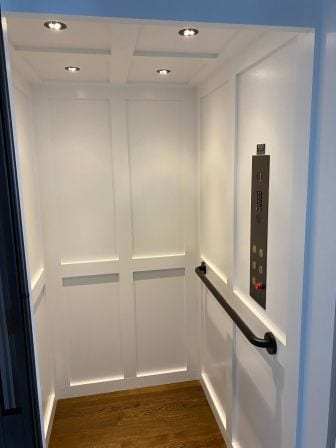Symmetry Home Elevator with White Shaker Car Panel and round turn back handrail